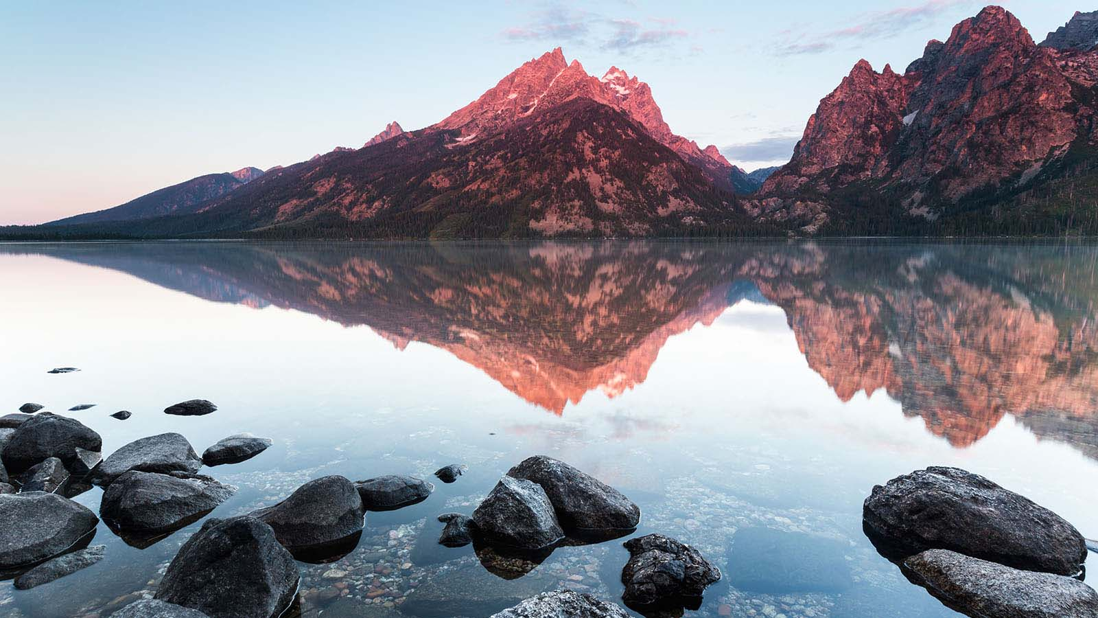 mountains reflecting into calm lake water
