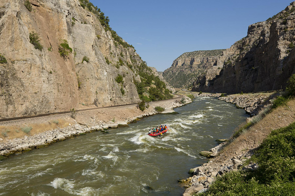 River running through canyon with white water rafters in the middle.