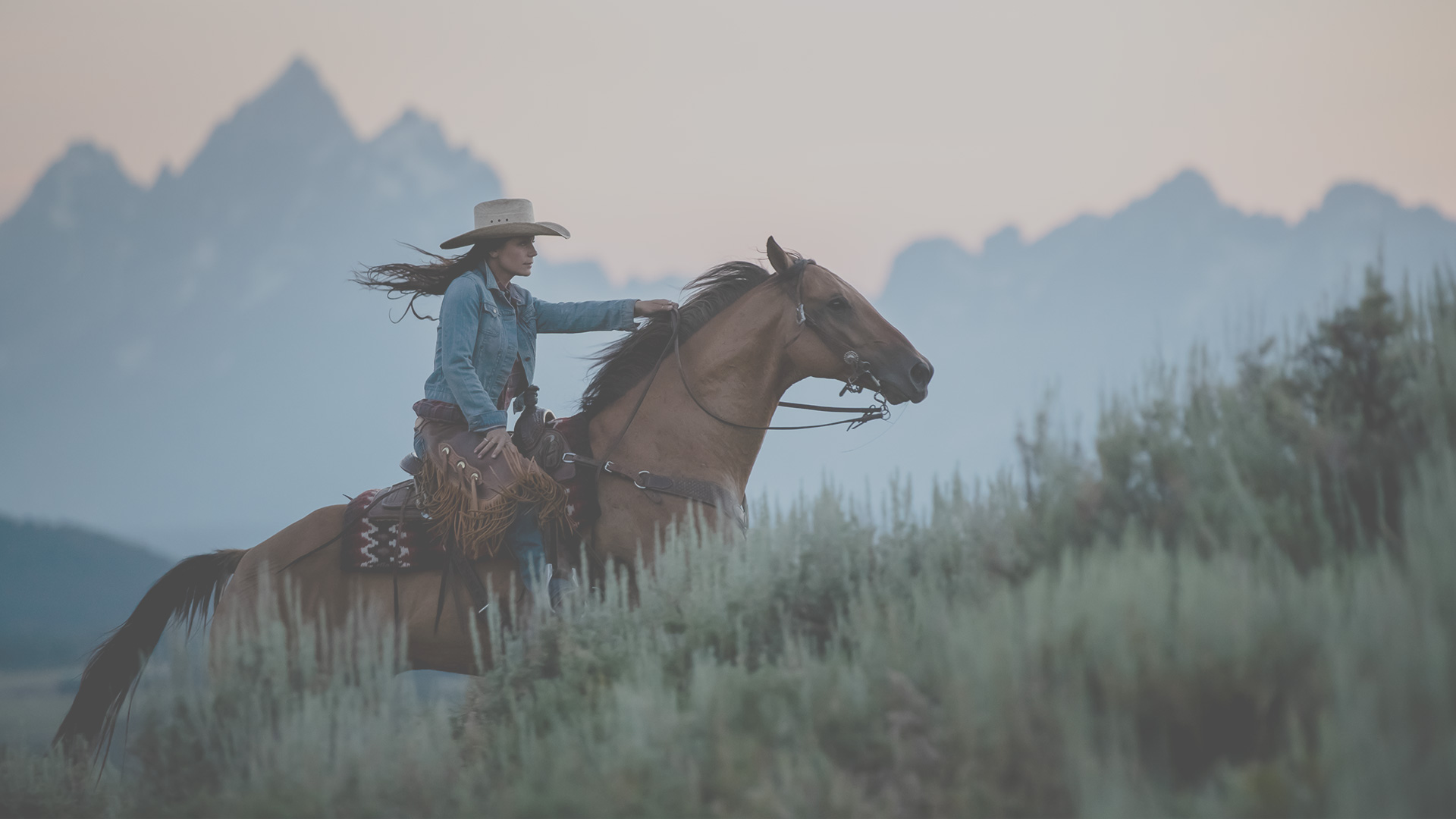 woman riding horse with grand teton mountains in the background