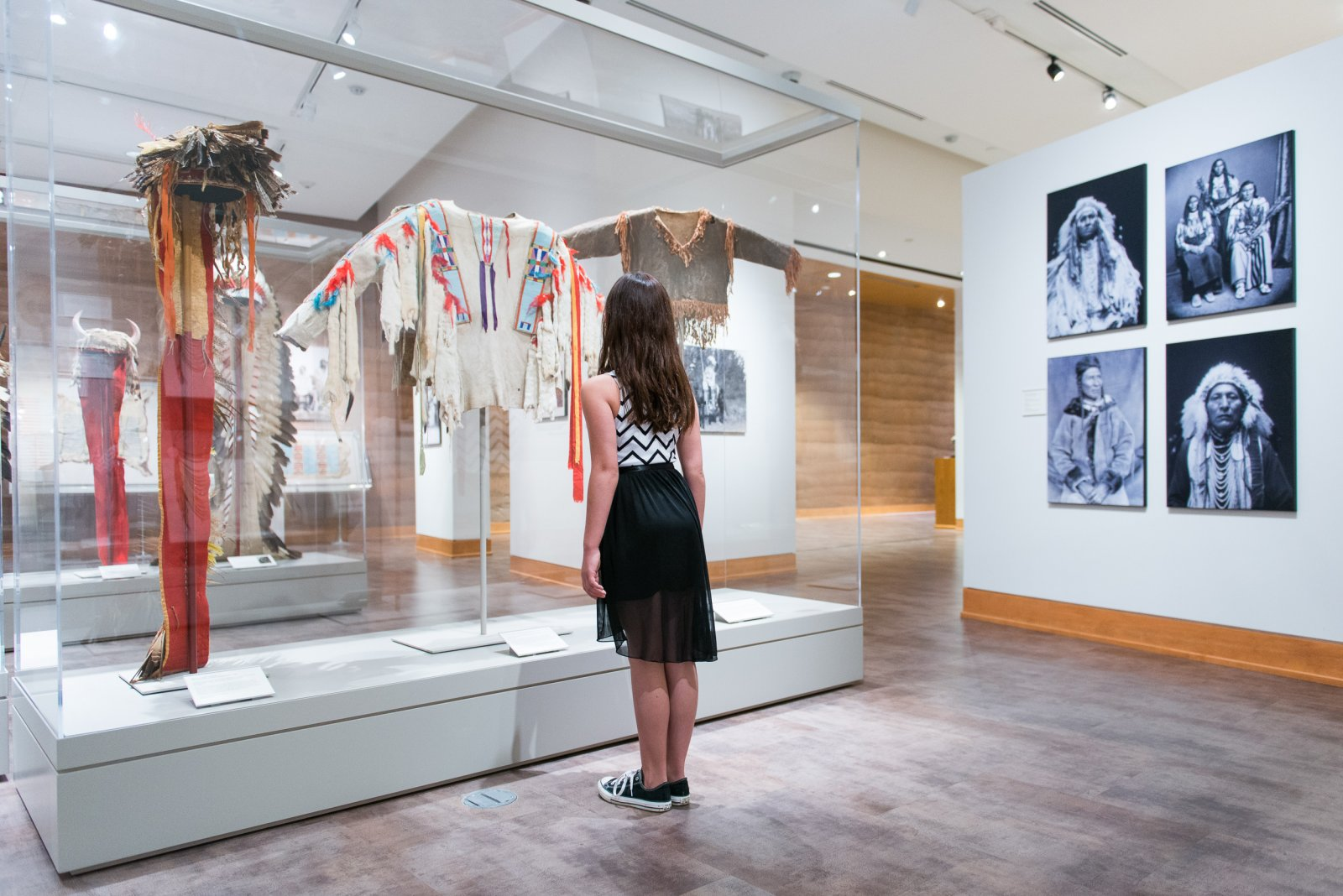 A girl in a black and white dress looks at a display of Native American clothing at the Brinton Museum in Sheridan, Wyoming.