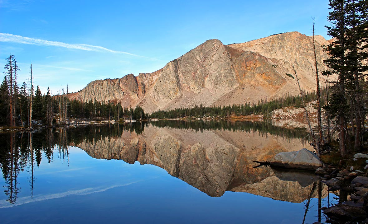A serene blue lake surrounded by mountains and green trees in Carbon County, Wyoming