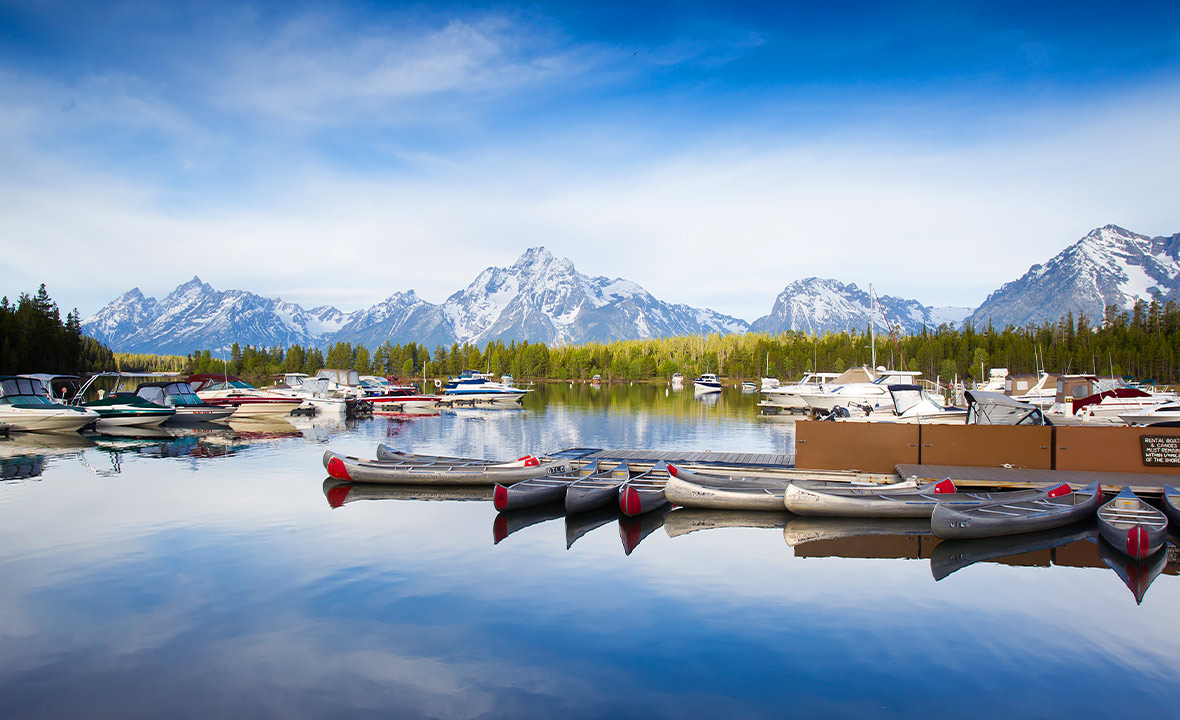 Rental canoes and boats sit atop the glassy waters with the majestic snow-capped mountains as a backdrop.