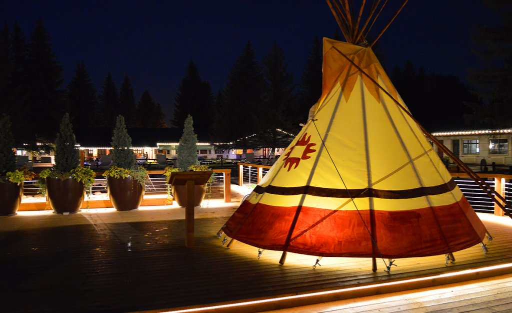 A teepee covered hot pool glows brightly in the night by the pool in Saratoga, Wyoming.