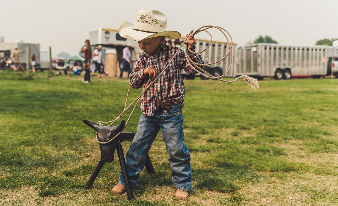A small young boy wearing a plaid shirt, blue jeans and a cowboy hat practices his rope wrangling skills on a black toy steer.
