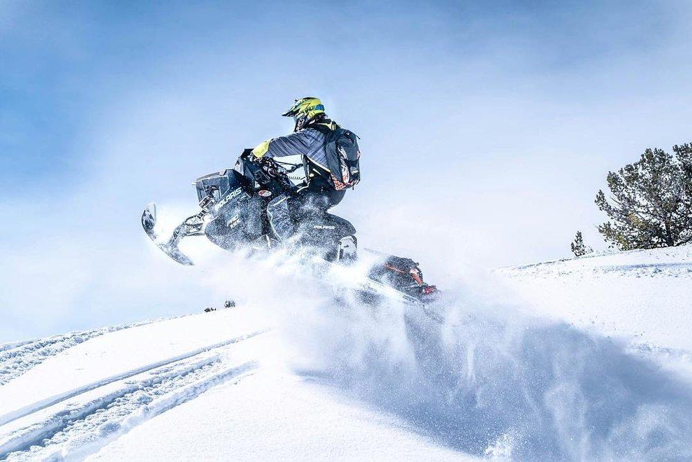 snowmobiler riding through the snow.