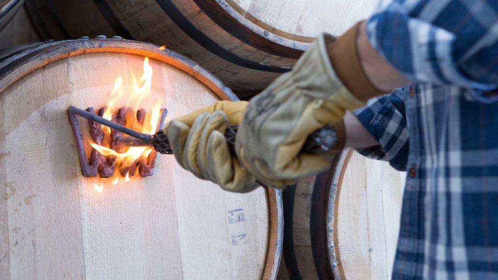 hands branding whiskey barrel