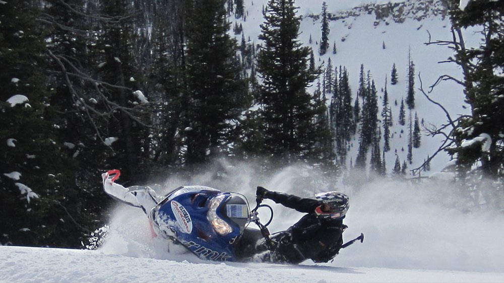 Snowmobile tearing up snow in forest
