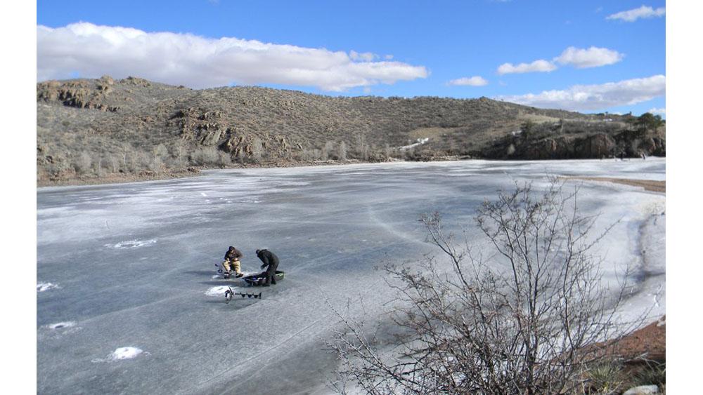 Fisherman on frozen lake with fishing access