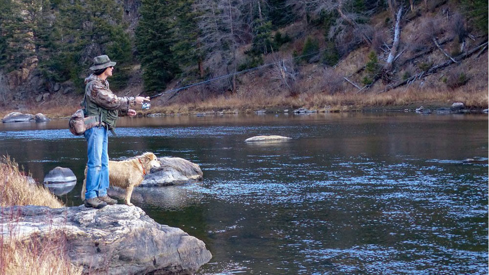 fly fisherman and dog on riverside