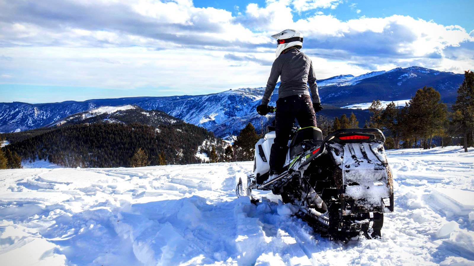Snowmobile rider overlooking grand view of mountainside