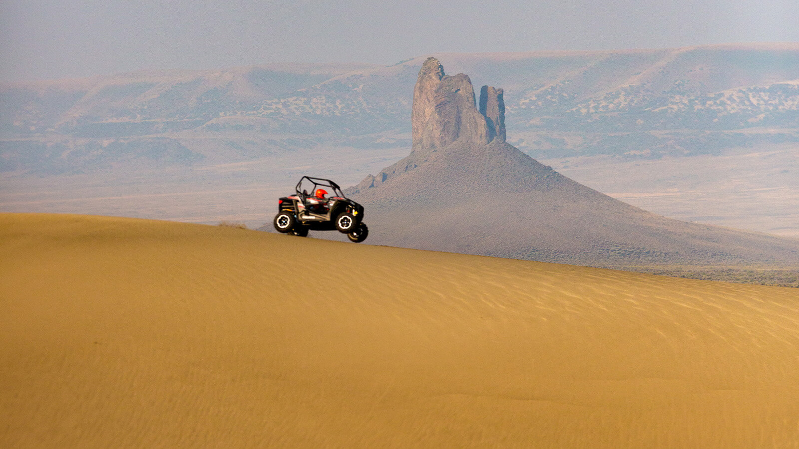 Off-road vehicle jumping a sand dune