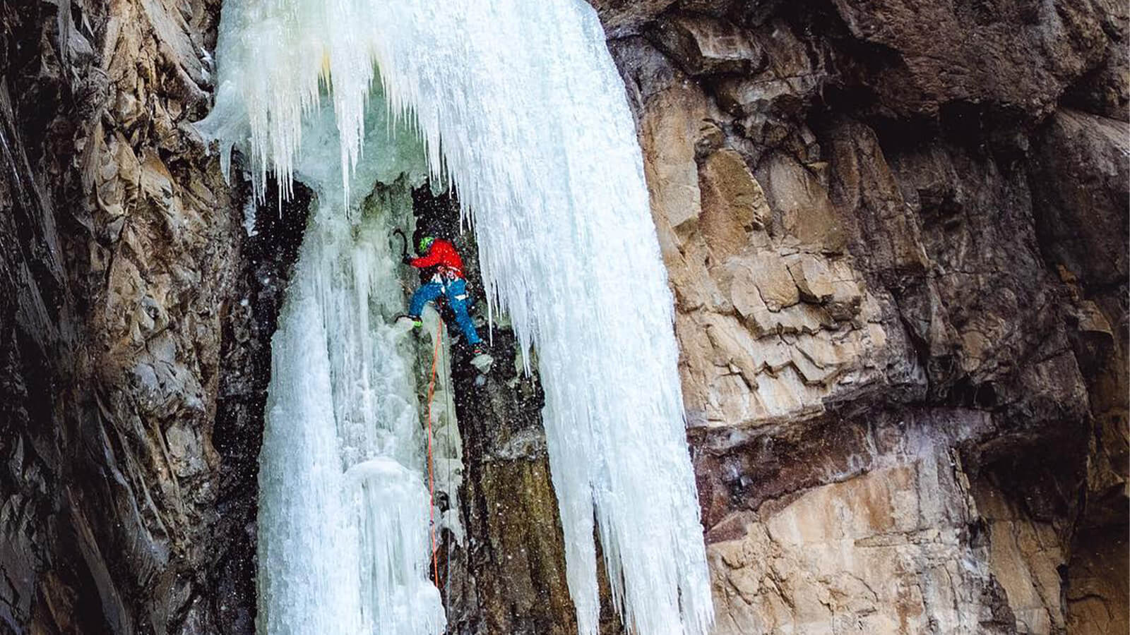 Ice climber scaling frozen waterfall