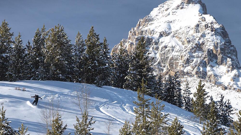 Snowboarder traversing powder covered mountainside