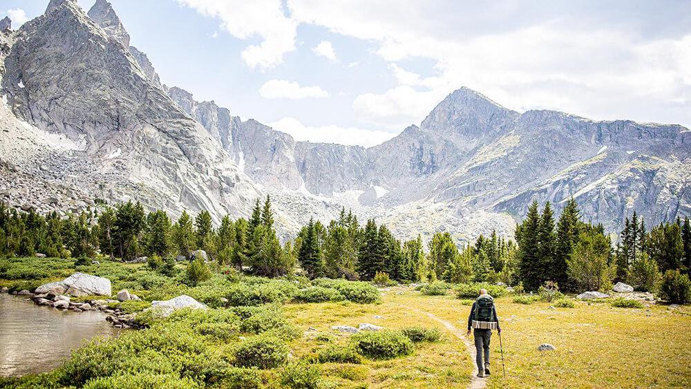 Hiker walking towards mountain range