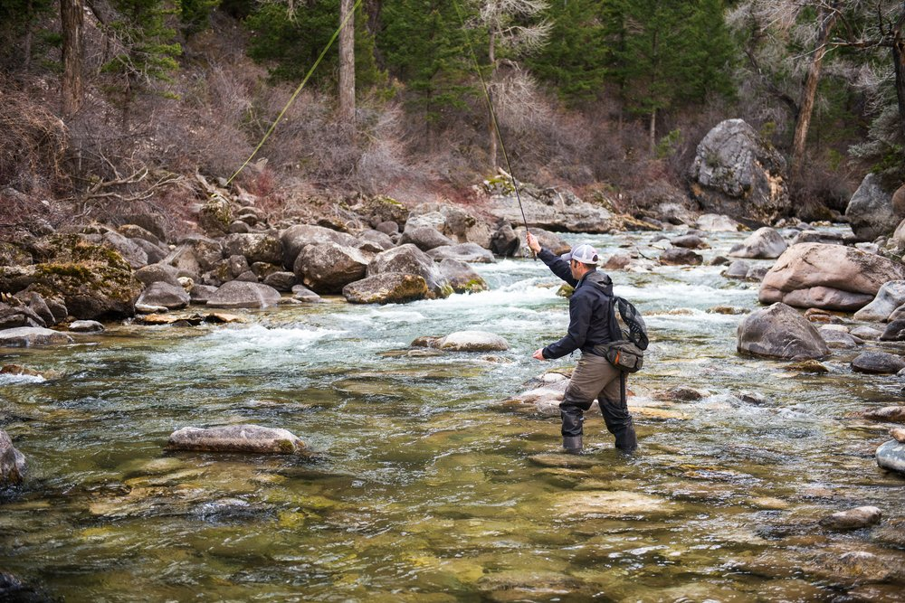 Fly fisherman in the middle of a river.