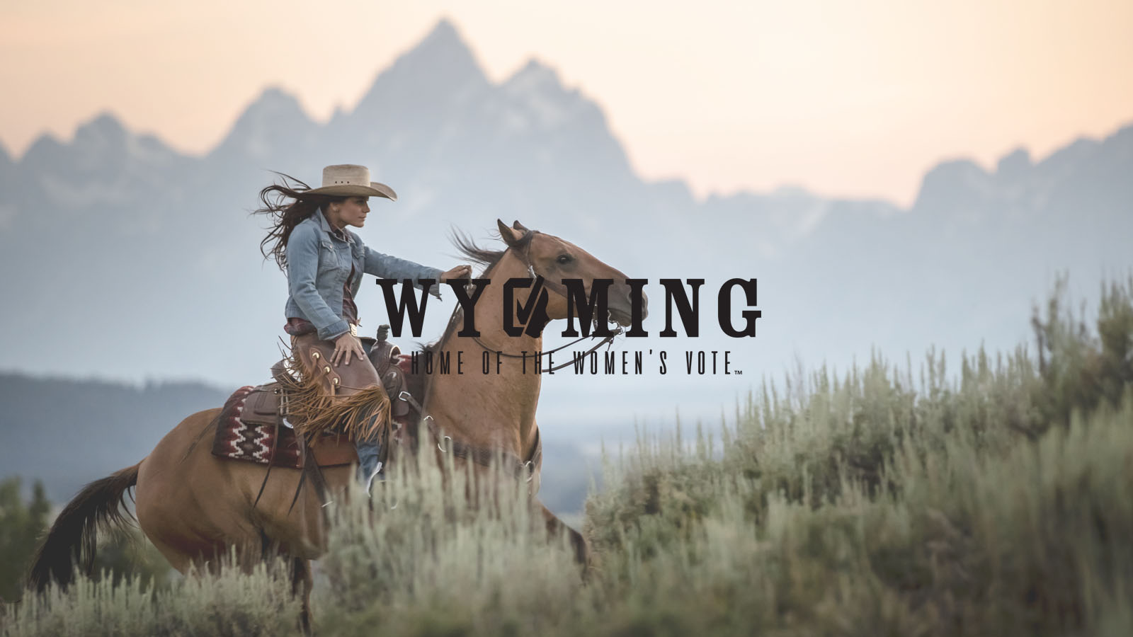 Woman riding horse in Grand Teton National Park with Women's Suffrage logo in black
