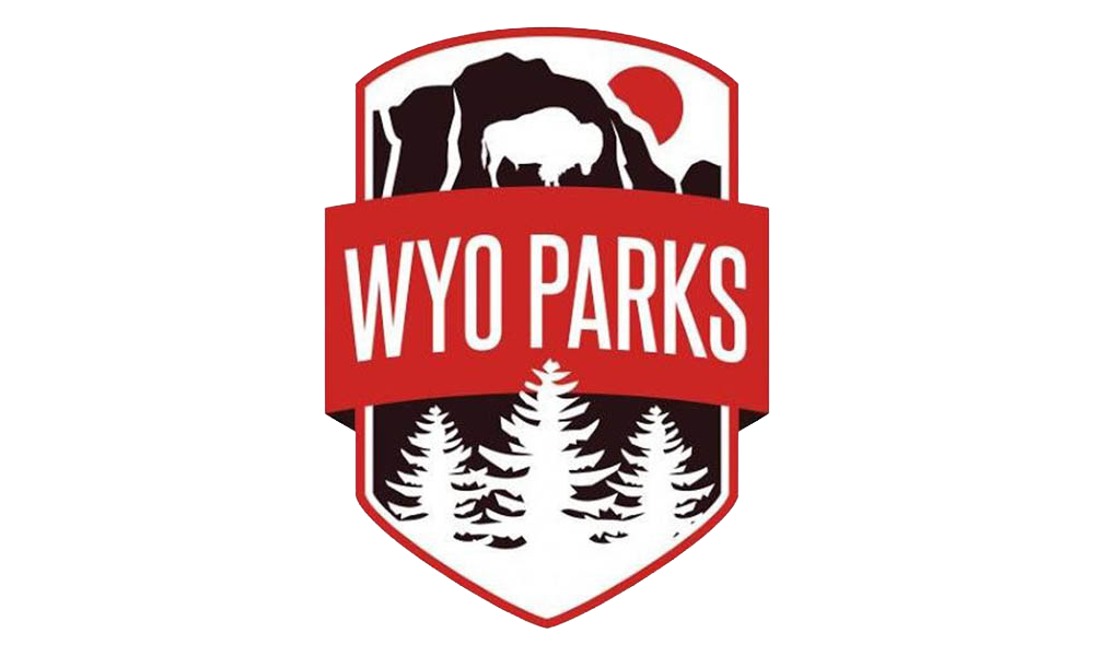 WYO Parks logo. White background with a brown cliff with a white Buffalo and trees in front of the cliff with a red banner with WYO Parks across it.