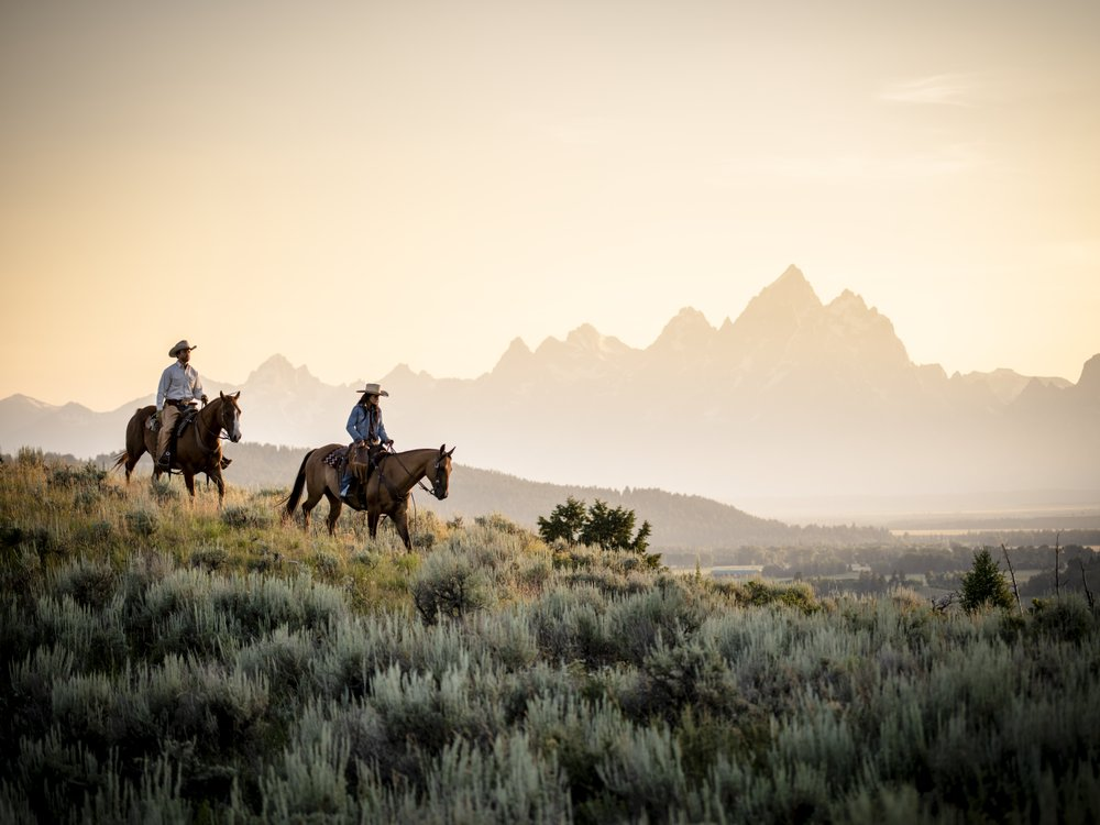 Riders on horses on a fogg morning in front of the tetons