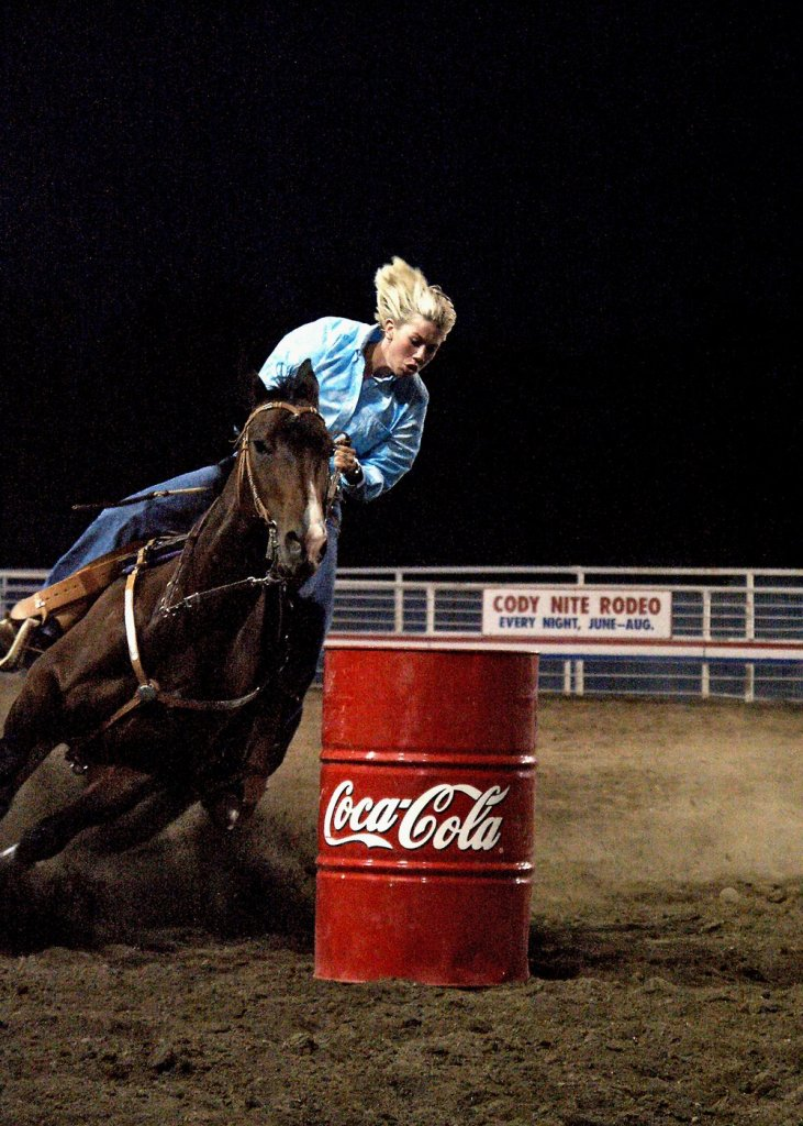 Lady on horse barrel racing.