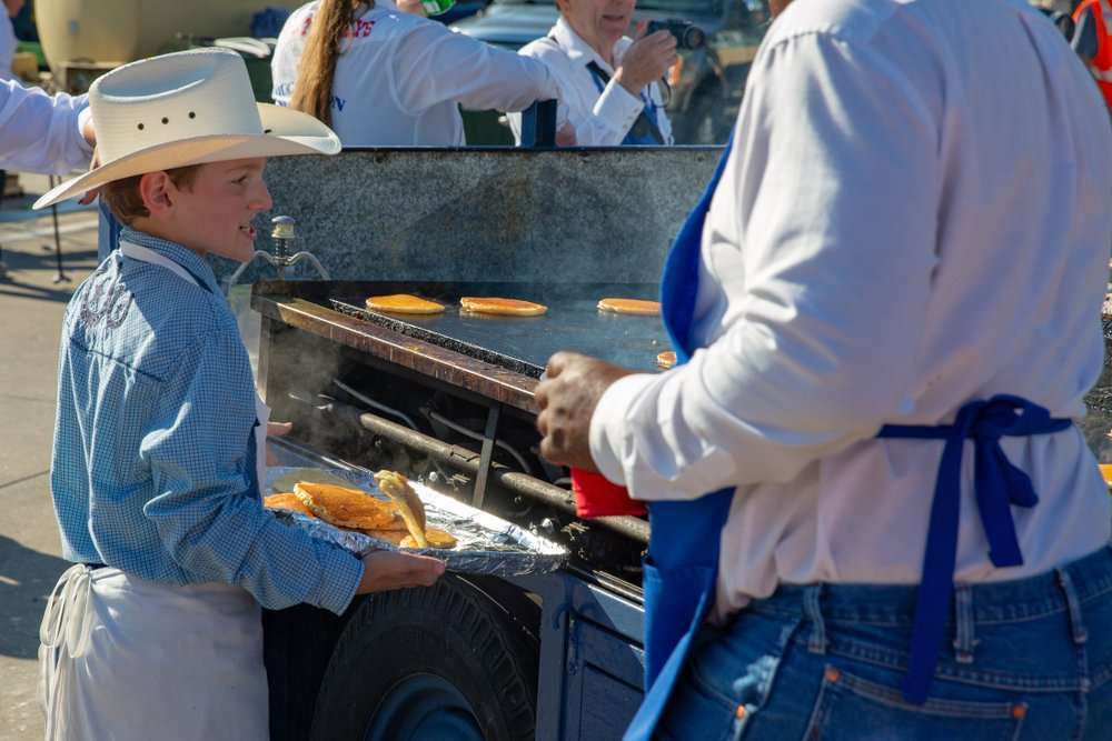 Boy scout helping catch pancakes during Frontier Days in Cheyenne, WY