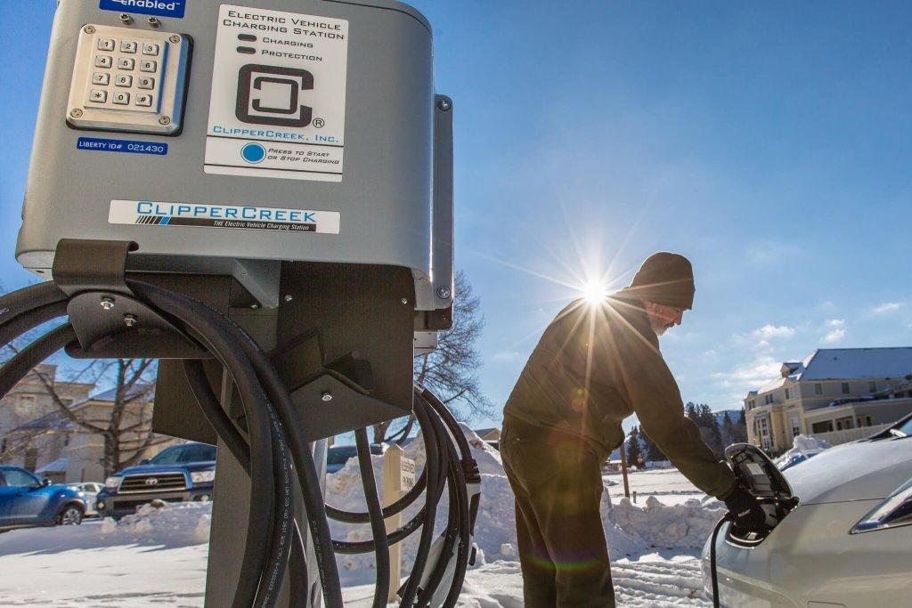 Man using electric car charging station.
