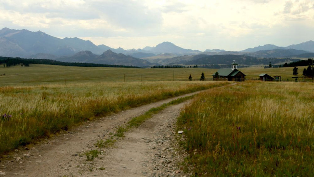 Dirt road through grass pasture with a country church in the background.