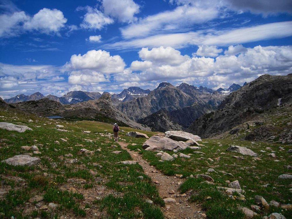 Man hiking across grass towards mountain range