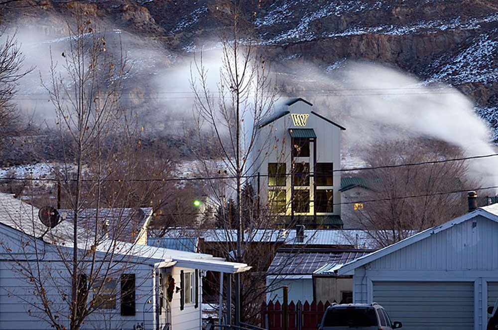 Houses in foreground with Wyoming Whiskey distillery behind them with mountains in the background.