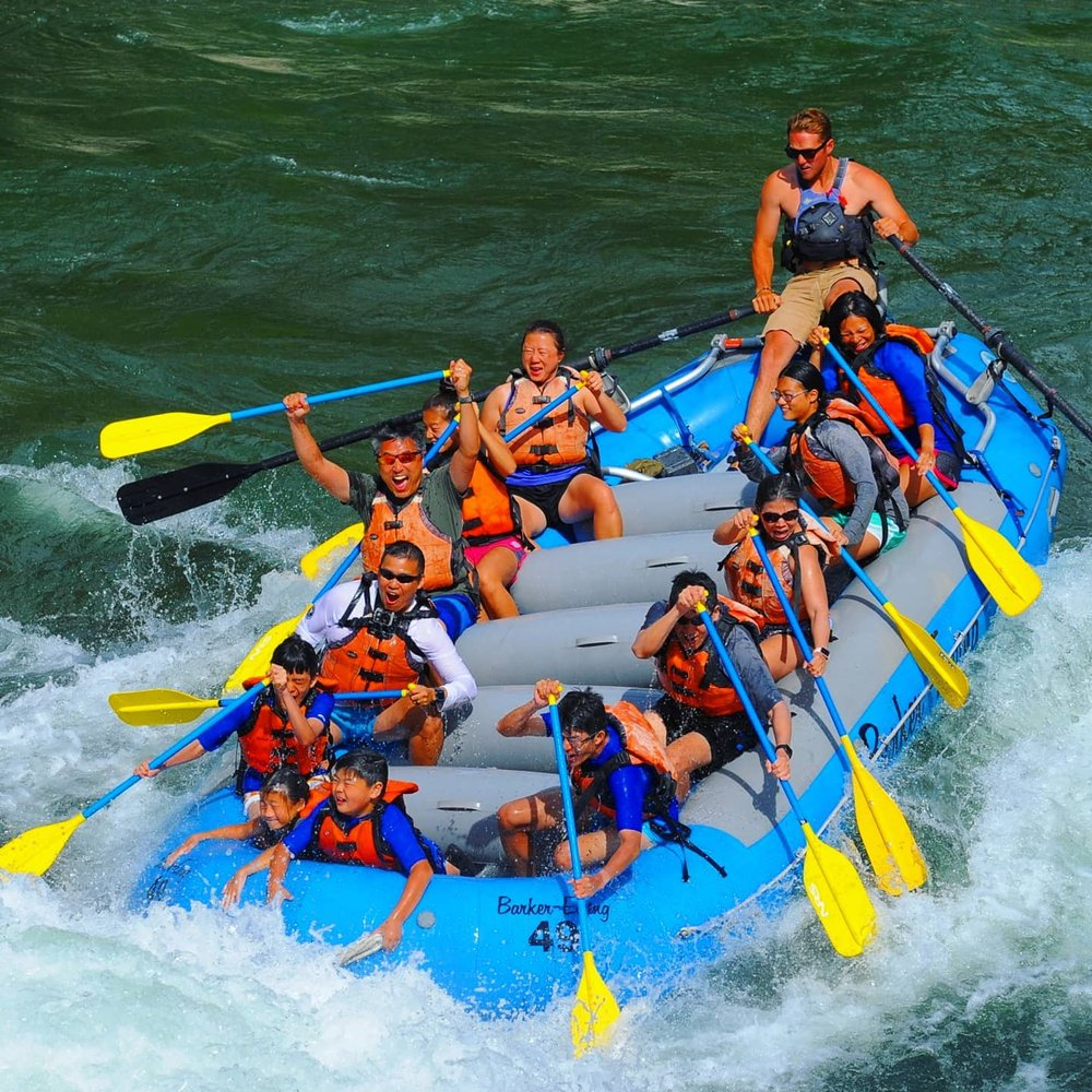 Raft with rafters paddling through rapids