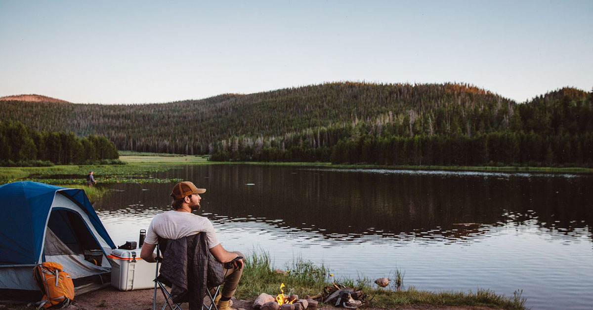 Man sitting at the edge of a river with a campfire.
