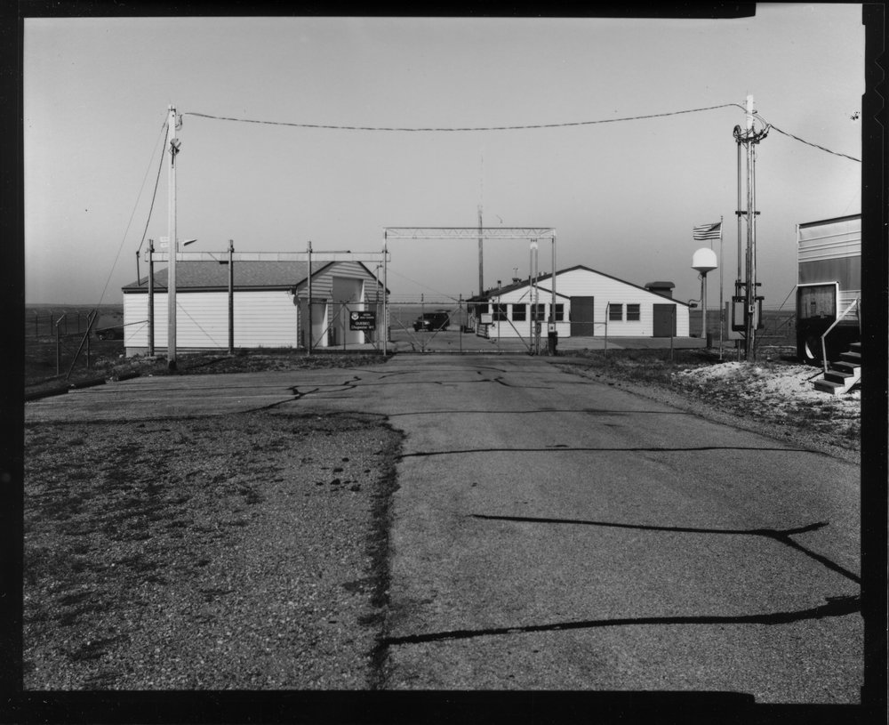 Black and white photo buildings behind gates.