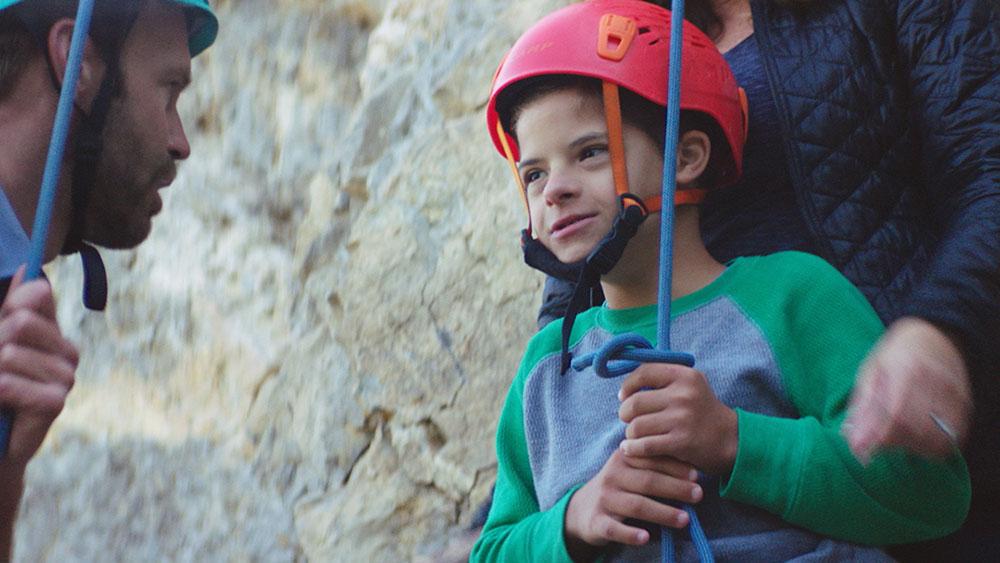 Little boy receiving instruction before beginning to rock climb
