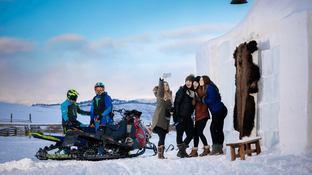 group of people in the snow next to snowmobiles