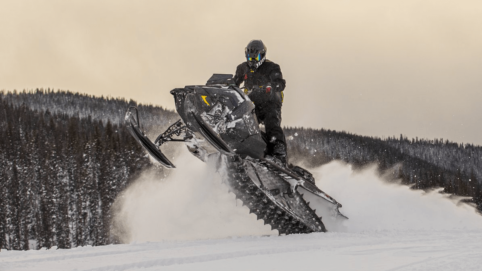 Snowmobiler jumping over some snow in the mountains.