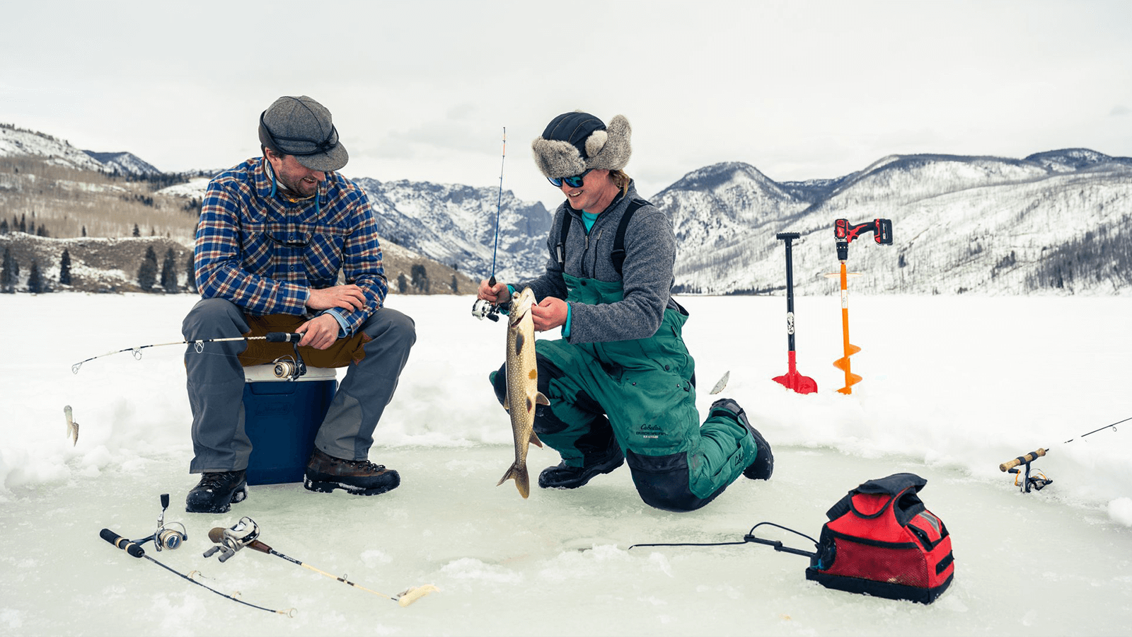 A couple guys ice fishing on a lake in the mountains.