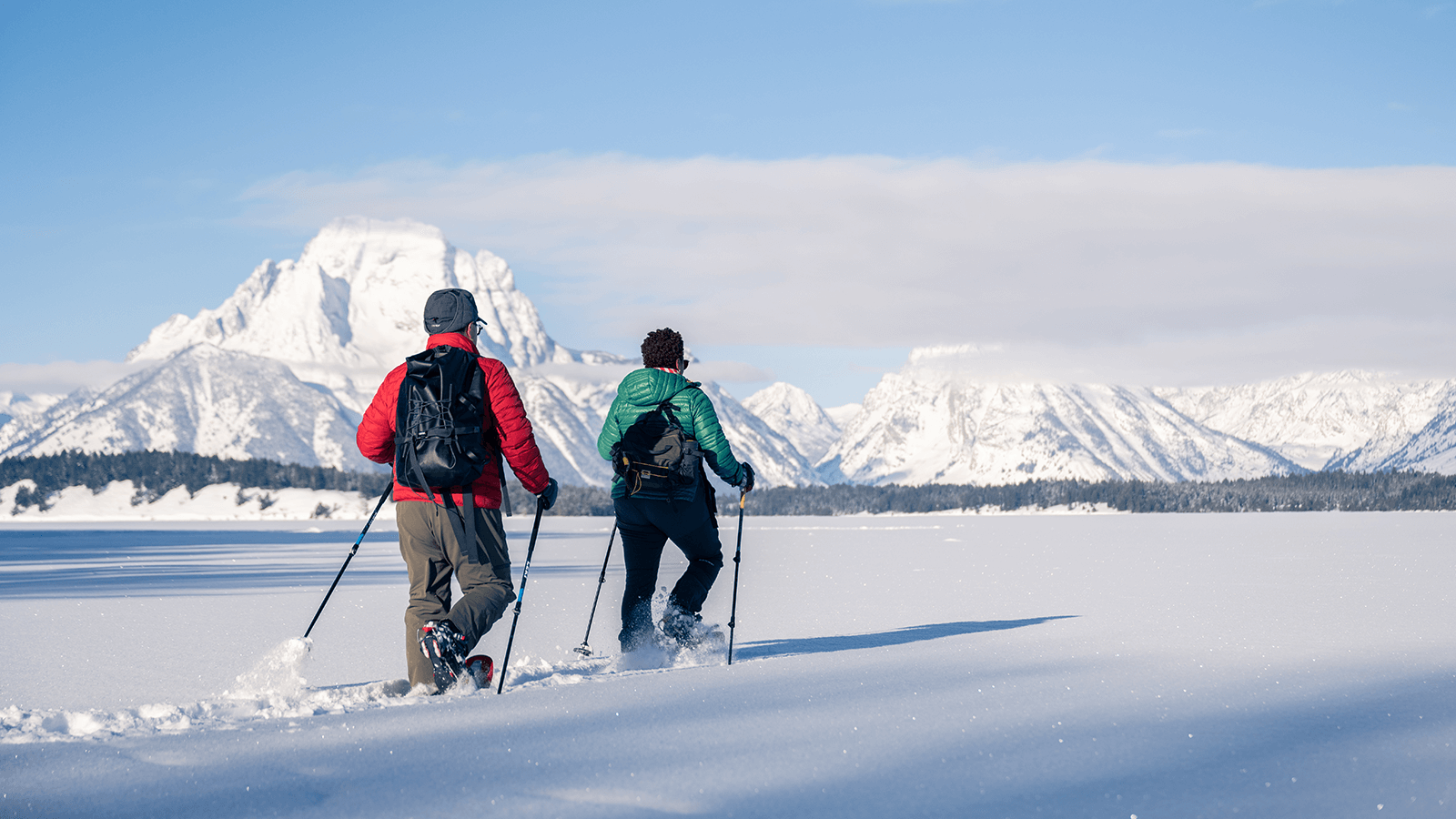 Couple snowshoeing through the snow, mountains in the background.